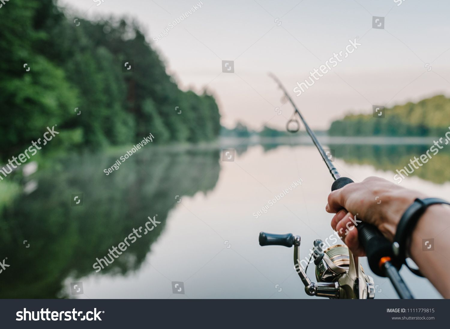 Fisherman with rod, spinning reel on the river bank  Sunrise