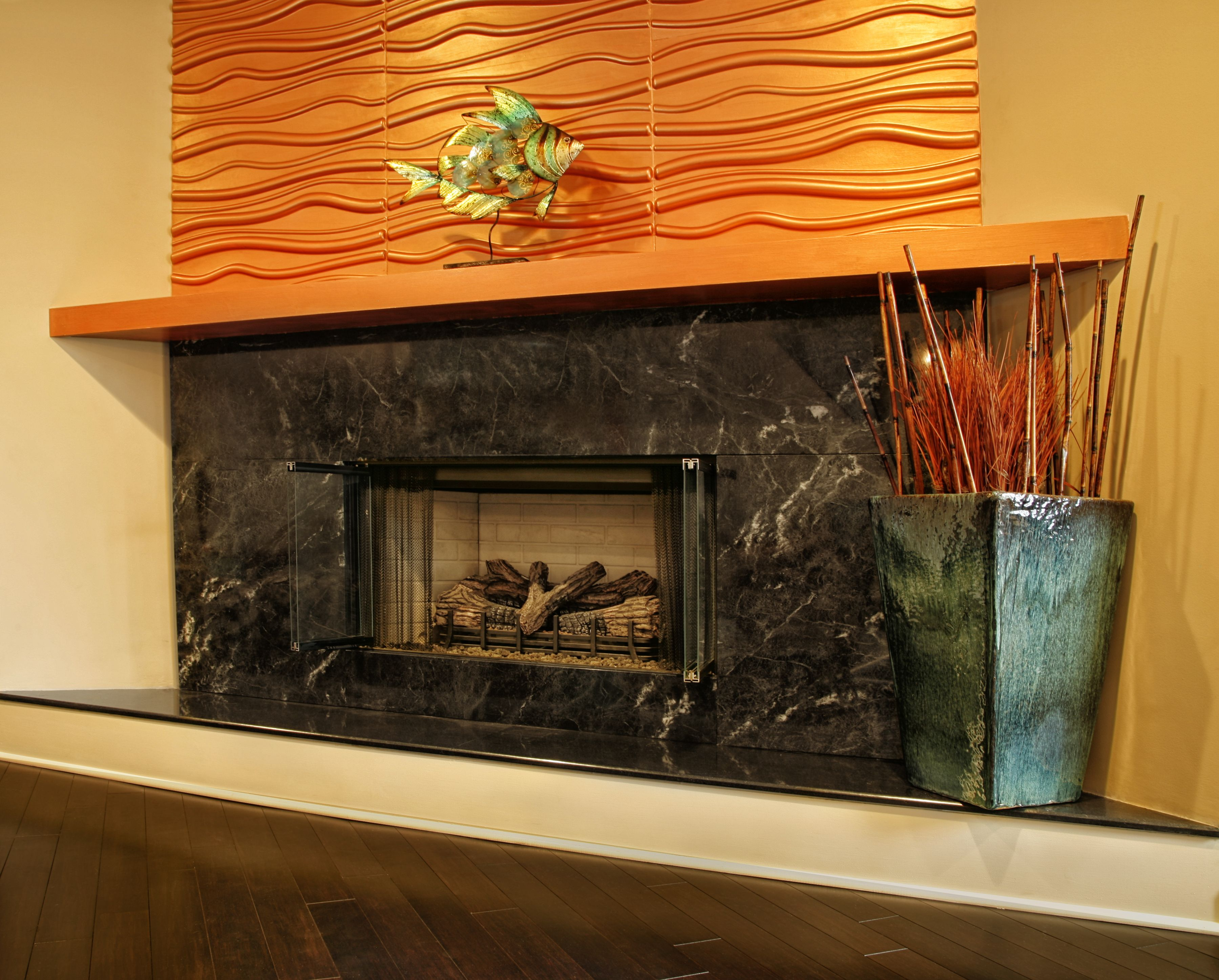 Copper Colored Textured Wall Panels Above A Portuguese Granite Fireplace