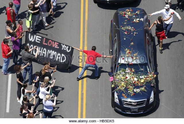 A well-wisher holding a banner touches the hearse carrying Muhammad Ali during the funeral procession for the three-time heavyweight boxing champion in Louisville, Kentucky, US on June 10th, 2016.    Contributor: REUTERS / Alamy www.alamy.com http://www.alamy.com/stock-photo-file-photo-a-well-wisher-holding-a-banner-touches-the-hearse-carrying-127354477.html