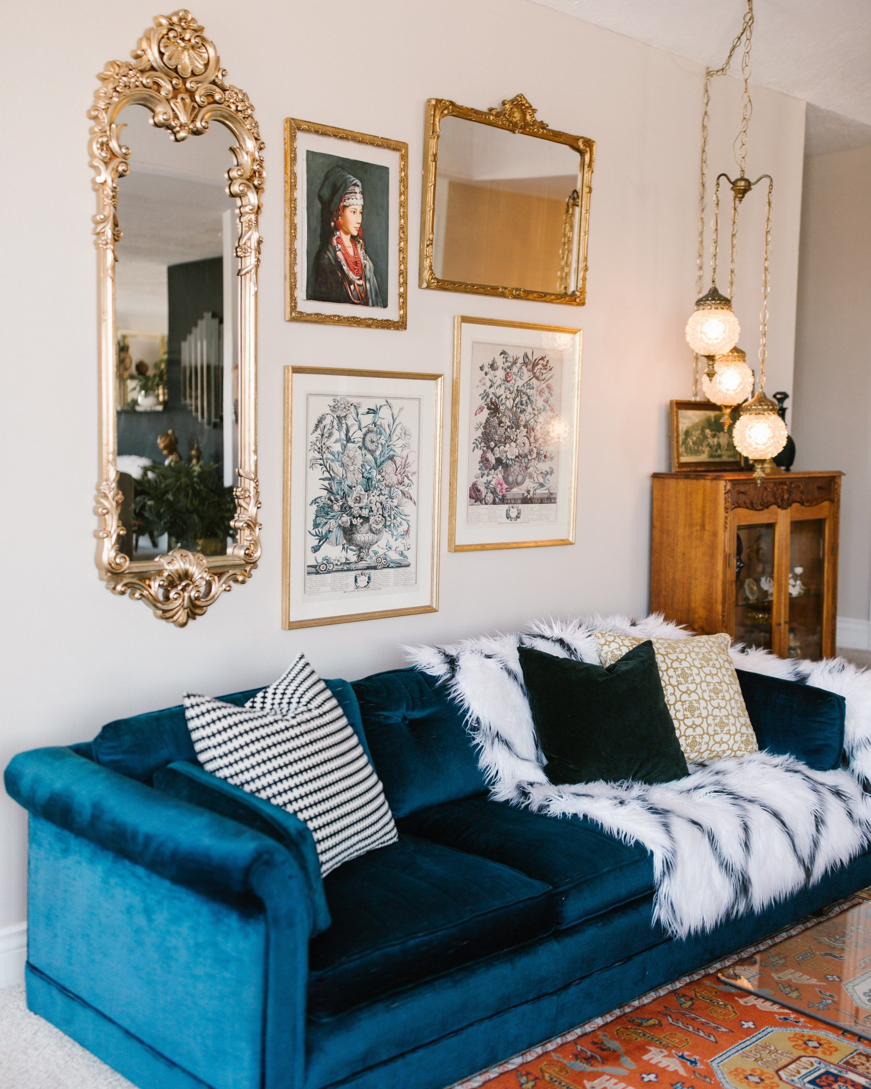 An Eclectic '70s Home Filled With Vintage Finds - Jenasie Earl - Vintage finds include this cobalt velvet sofa, swag lighting, mirrors and artwork. #gallerywall #vintagedecor #eclecticinteriors #eclecticdecor #velvetsofa #vintagedesign #swaglighting #interiordecor #interiordesign #homedecor #interiordecor #eclectichome #housetour #interiors