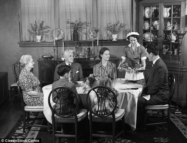A family gathers round the table in the 1940s as they are served roast turkey by their maid