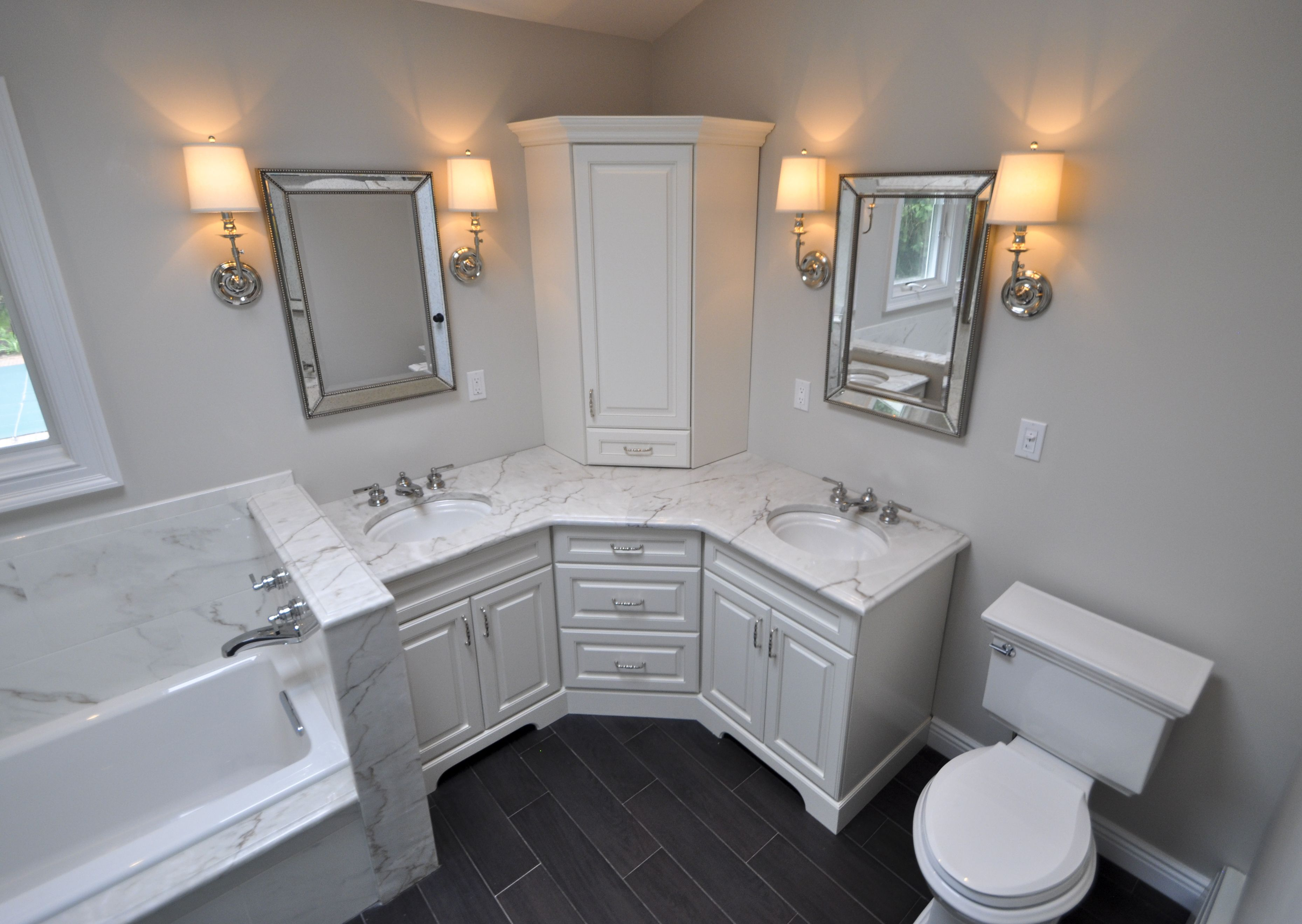 Custom Master Bathroom With Double Corner Vanity Tower Cabinet Wall Sconces Toilet And Built