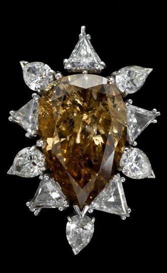 Impressive cognac colored pear shaped diamond pin   Center pear shaped diamond weighing approximately 12.4 carats, of cognac color framed by triangular and pear shaped diamonds.