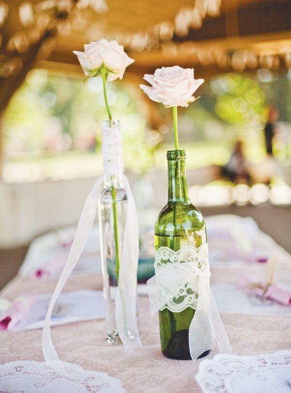Botellas, lazos y flores para decorar una mesa de fiesta.
