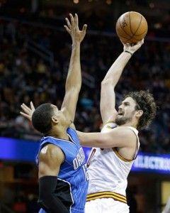 El delantero de poder de Cleveland Cavaliers', Kevin Love, lanza un gancho sobre la defensa del jugador de Orlando Magic's, Tobias Harris, en el cuarto parcial del partido celebrado anoche.
