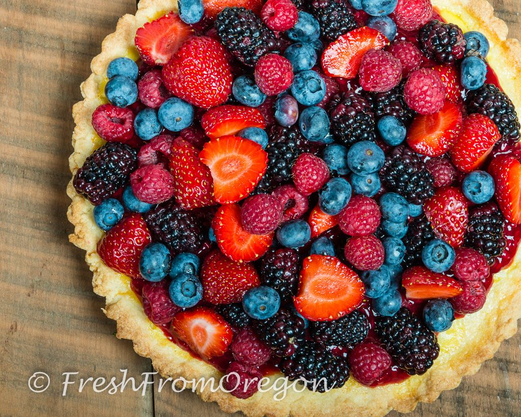Fresh Oregon Berry Tart | The sugar cookie crust in this tart is sweet and crisp and much firmer that a traditional pie dough crust making it last a few extra days in the refrigerator without getting soggy.  The sweet taste of the lemon filling with the sauce from the tayberries and the mountain of berries creates layers of flavor from top to bottom. @carrietrax