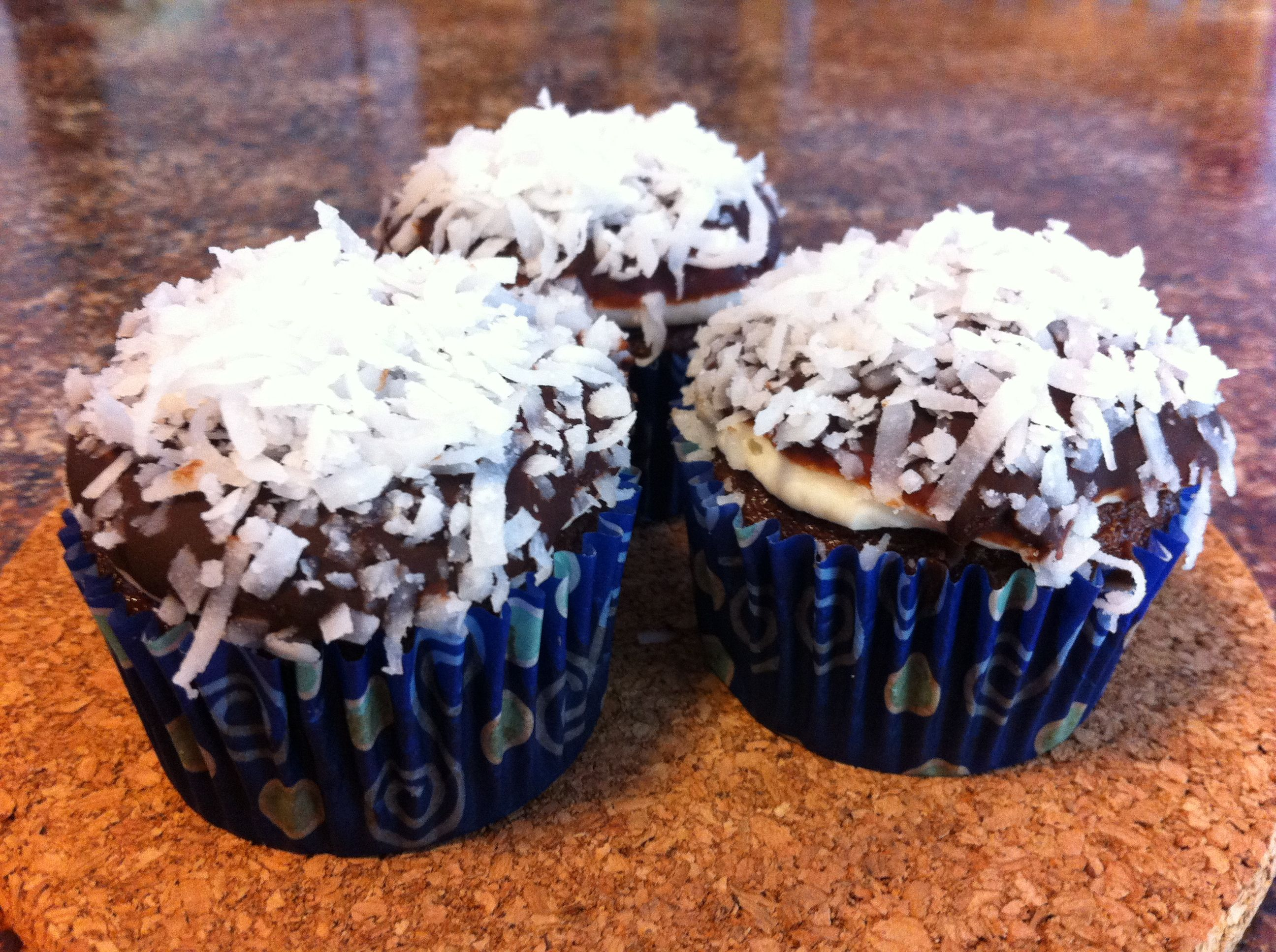 Almond Joy cupcakes- chocolate ganache dipped almond devil's food cupcakes with coconut icing.