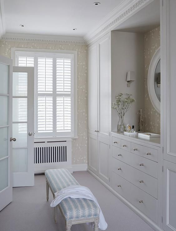 Cottage Closet Features Gray Built In Cabinets Flanking A Dresser Under White Oval Mirror Alongside Blue French Bench