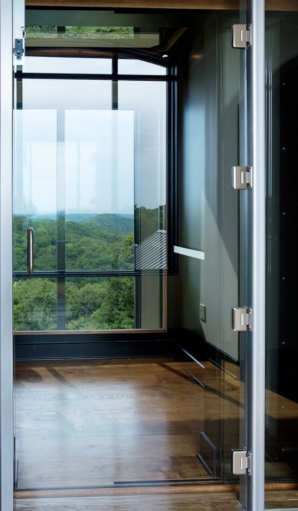 Homelift inc glass elevator provides a stunning view for Custom home elevators