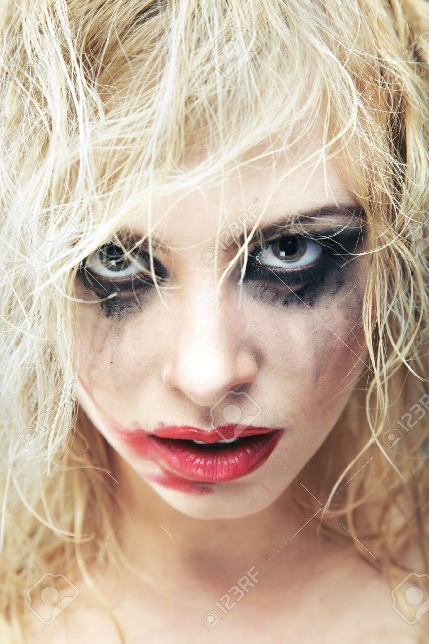 Blond lady with bizarre makeup and smeared lipstick on her face