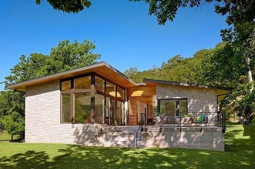 jolie maison contemporaine en bois et pierre surplombant un lac texan