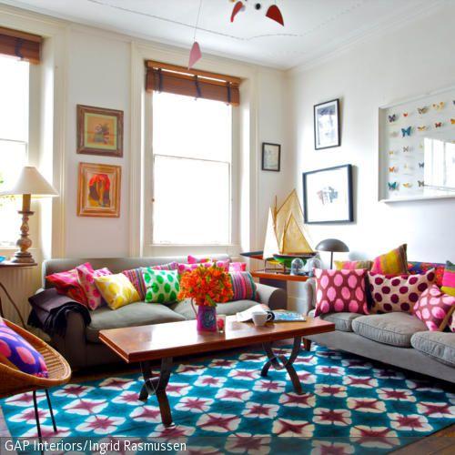 Die bunten Dekokissen verleihen dem Wohnzimmer ein Eigenleben und heben durch ihre knalligen
