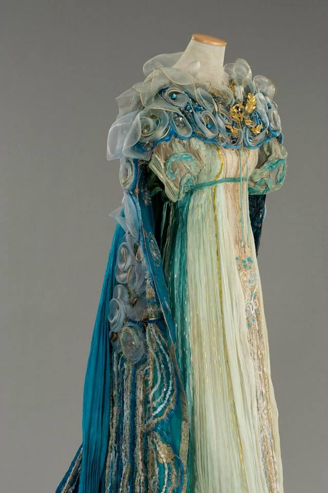 "Costume:Gabriella Pescucci in 1998. ""Queen Titania"". organza is in tones ranging from ivory to teal, with the central panel embroidered chenille yarns, golden threads and green stones.The mantle, with its interior of blue georgette fabric all gold and silver wire, consists on the combination of large edges and silk embroidered inserts with large pleated blue silk drapes. The embroidery, are a variety of materials including: chenille wires, wires gold, azure stones and nylon tulle. Detail"