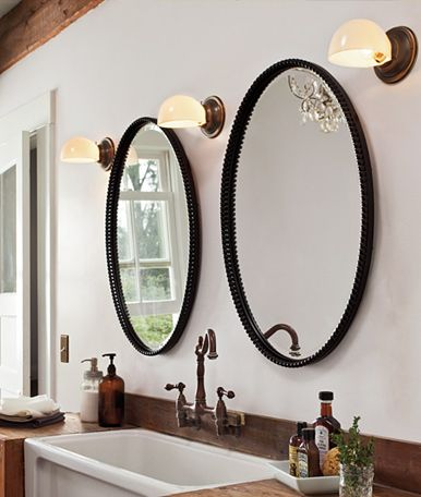 Two Round Mirrors And Three Sconces In Rustic Bathroom