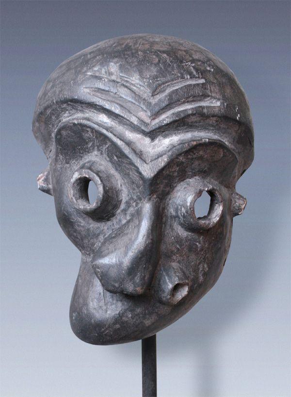 Mbuya sickness-mask mbangu, Pende -tribe, Congo  Charakterstarke Maske die durch die verzerrten, entstellten Gesichtszüge eine schwere Erkrankung darstellt (Lähmung, Schlaganfall oder Frambösie), Reste von weissen Pigmenten. Die weit aufgerissenen tubusförmigen Augen und Mund deuten auf eine Beeinflussung durch die östlichen Pende hin.   Maße  ca. 23 x 17 x 8 cm