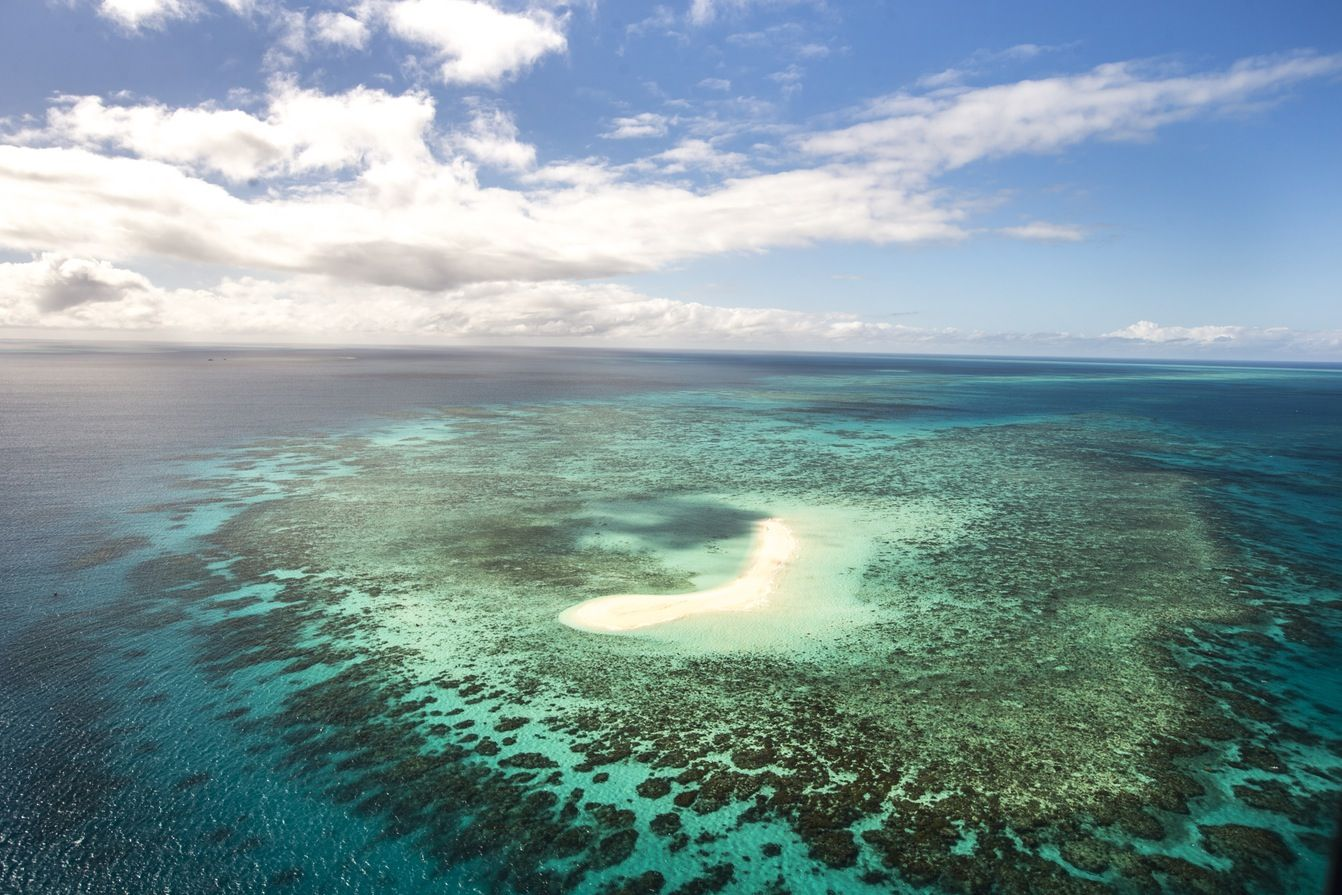 A small island and fringing reef seen from the air. The Great Barrier Reef is the largest coral reef ecosystem on the planet composed of almost 3000 individual reefs. Queensland, Australia.