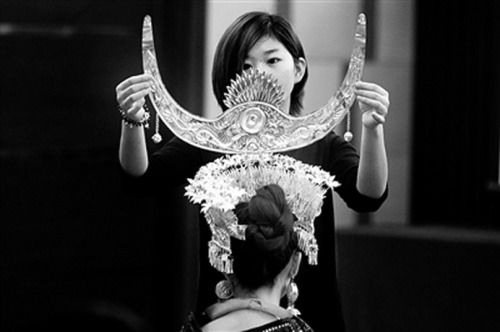 A Hmong silver headdress is carefully adjusted.