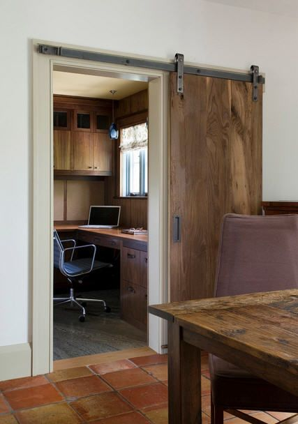 A rustic yet industrial-style sliding barn door was installed to close off this home office that is just off of the kitchen