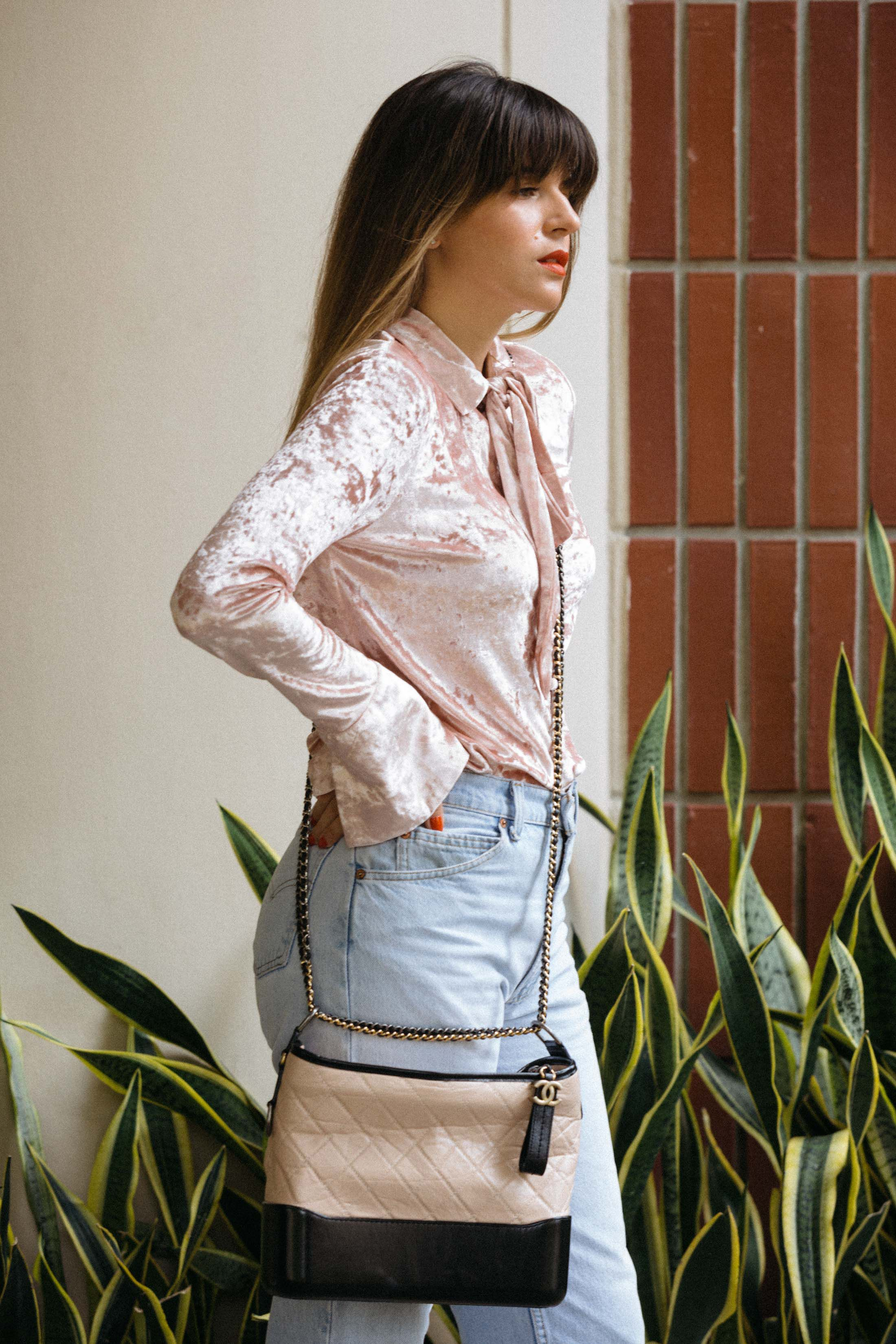 8a8ca1f1a31fbb Maristella wears a pink velvet blouse, high rise jeans and Chanel cross  body bag