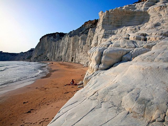 The beach at the base of Scala dei Turchi, a rocky cliff on the coast of Realmonte, is strikingly scenic. Its fiery bronze sands are a stunning contrast to the azure ocean in front, and the pale gray cliffs behind. The area is famous for being one of Sicily's most beautiful natural wonders.