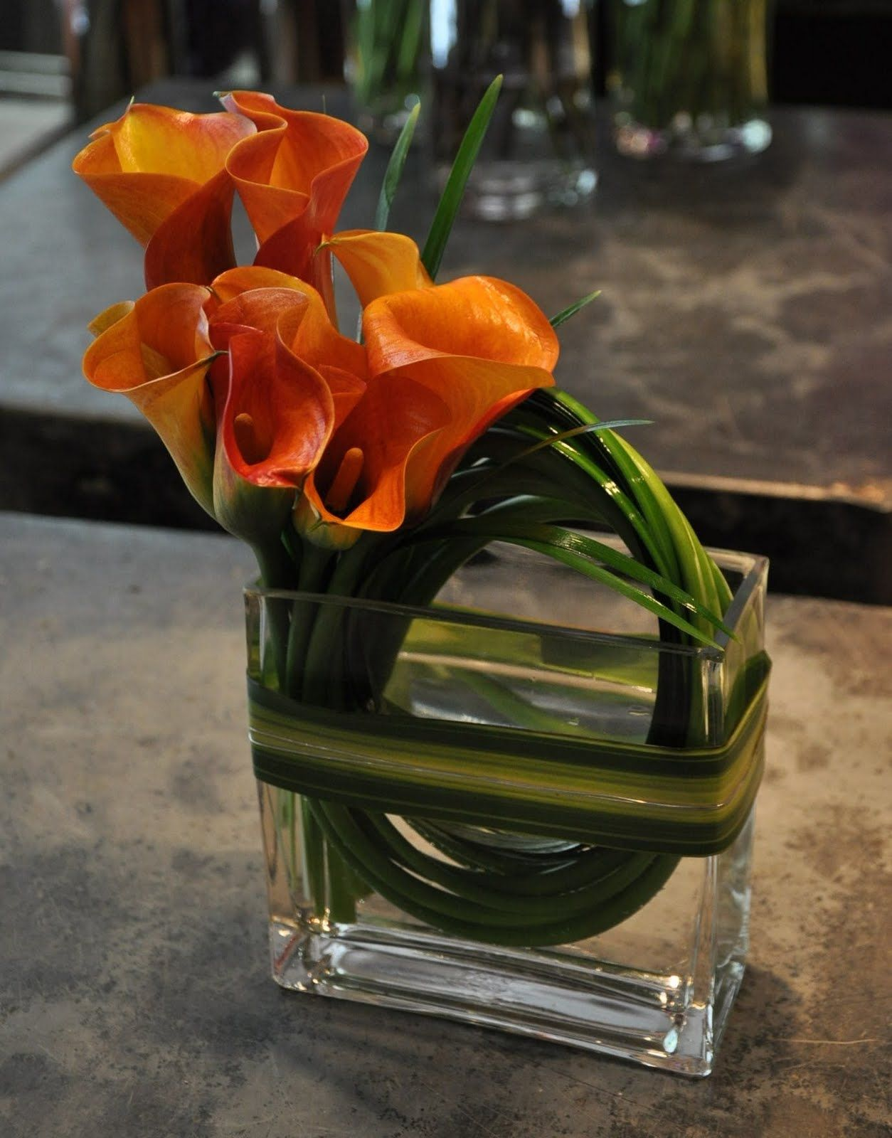 Mango callas with bear grass and wrapped with variegated leaves in mango callas with bear grass and wrapped with variegated leaves in tall rectangle glass reviewsmspy