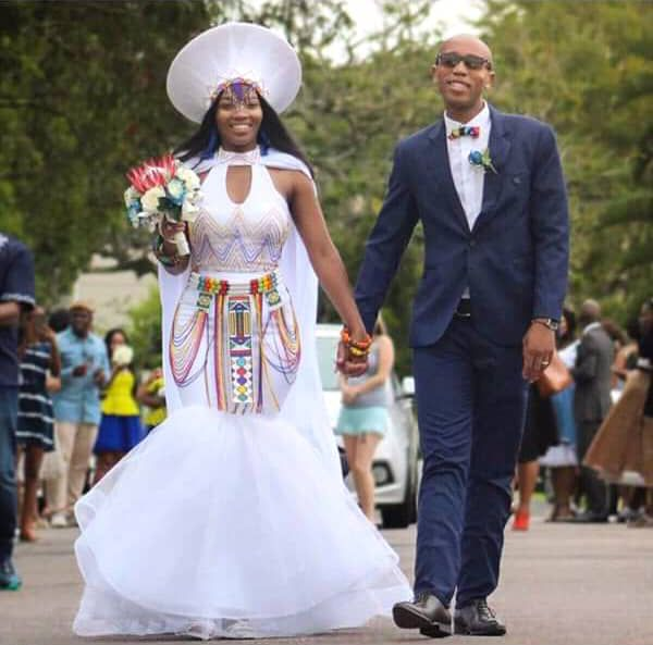 Bride In Modern Zulu Traditional Wedding Dress With Cape Isicholo Hat Beads Zulu Traditional Wedding Dresses African Traditional Wedding Dress African Traditional Dresses