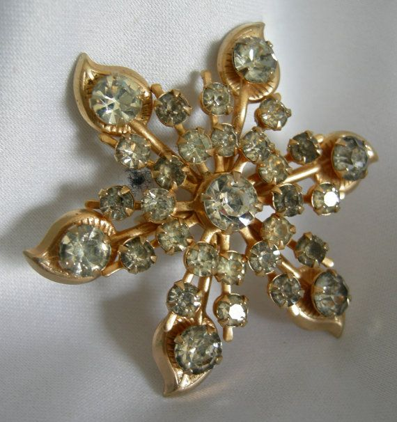 Lovely and lightweight gold tone brooch studded with prong set rhinestones. Measure 1 7/8 in diameter. In very good preowned vintage condition.