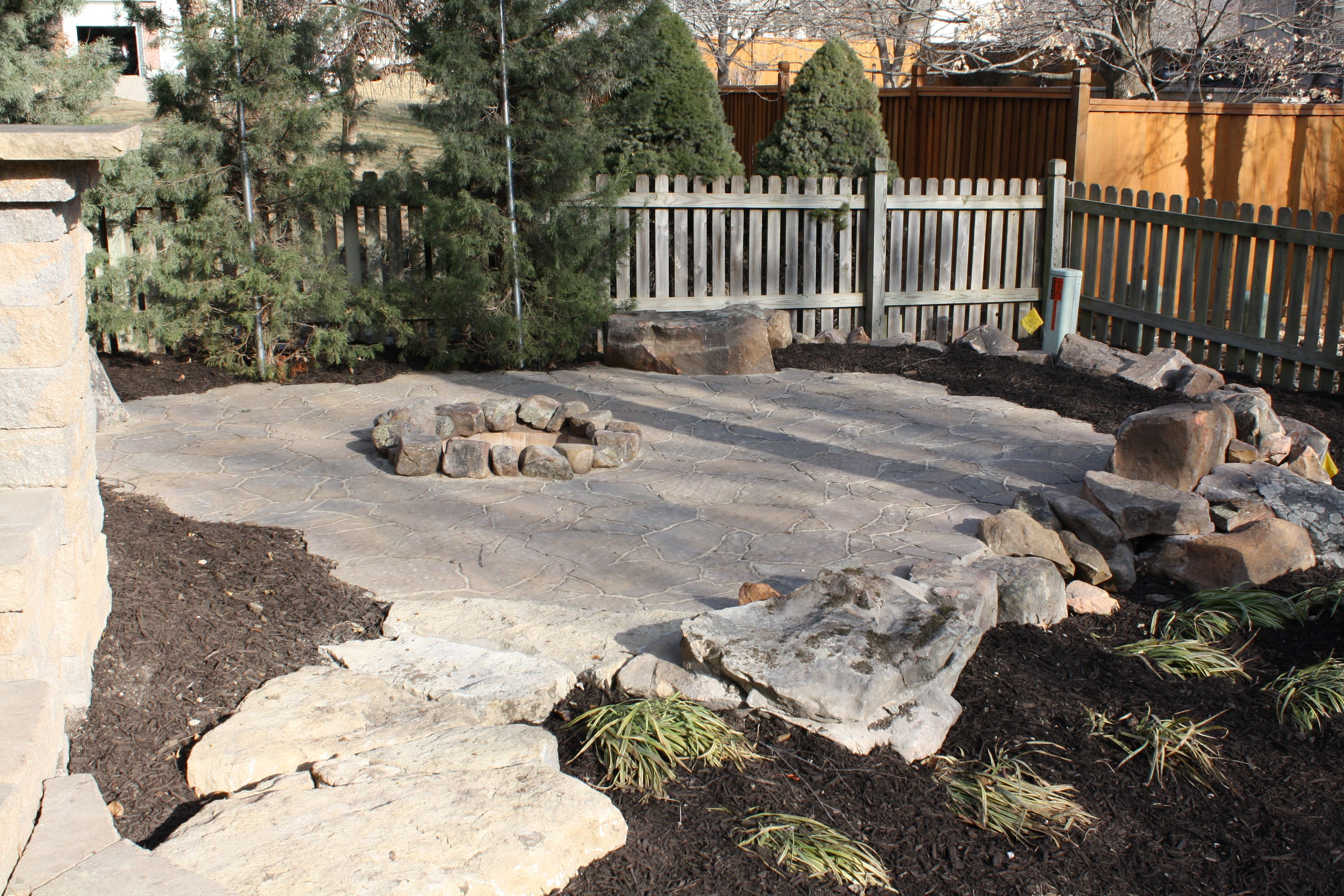 in ground wood burning fire pit inset into paver patio with