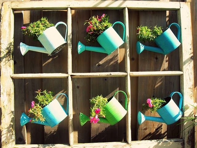 Old window frame and dollar store watering cans.  Cans are attached to the window frame using small nails.  Fill with plants.  Hang!  Totally inspired!
