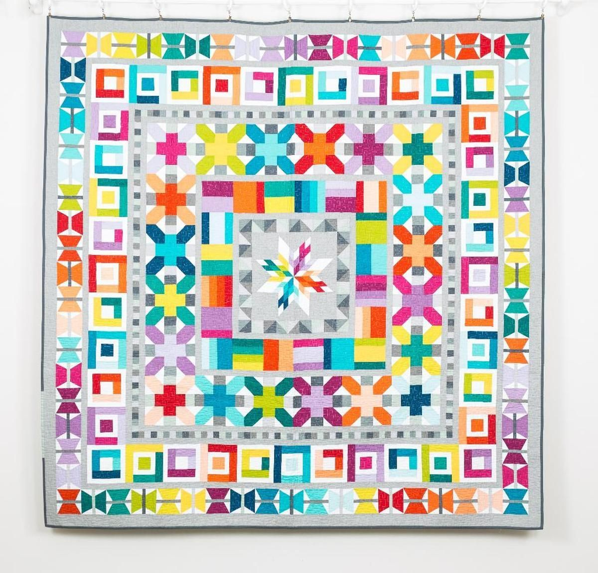"""Create a quilt as captivating as summer fireworks with the Aviatrix Medallion Quilt Kit! Your kit includes a pattern and Fat Quarter pre-cuts from the vibrant Elizabeth Hartman Designer Palette by Kona Cotton. Featuring radiant hues like Emerald green, Celestial blue and Valentine pink, this lush collection is the perfect pairing for the dazzling, geometric style of the 80"""" x 80"""" Aviatrix quilt top. Harmonious colors and an incredible array of shapes combine for a quilt that will l..."""