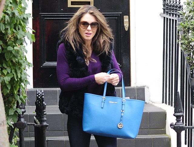 Elizabeth Hurley carries a blue MICHAEL Michael Kors Jet Set Travel Tote.