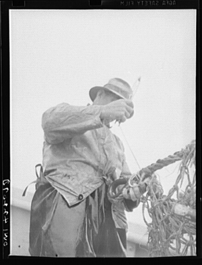 On board a fishing vessel out from Gloucester, Massachusetts. Mending the forward end of the wing of a net Photographer Howard Liberman Created September 1942