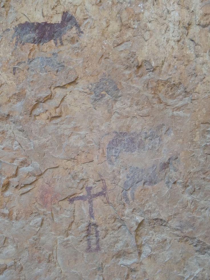 Escena de caza pintada con pigmentos rojizos sobre la piedra. En su centro vemos un arquero disparando a unos animales cuadrúpedos. En la parte superior vemos un caballo