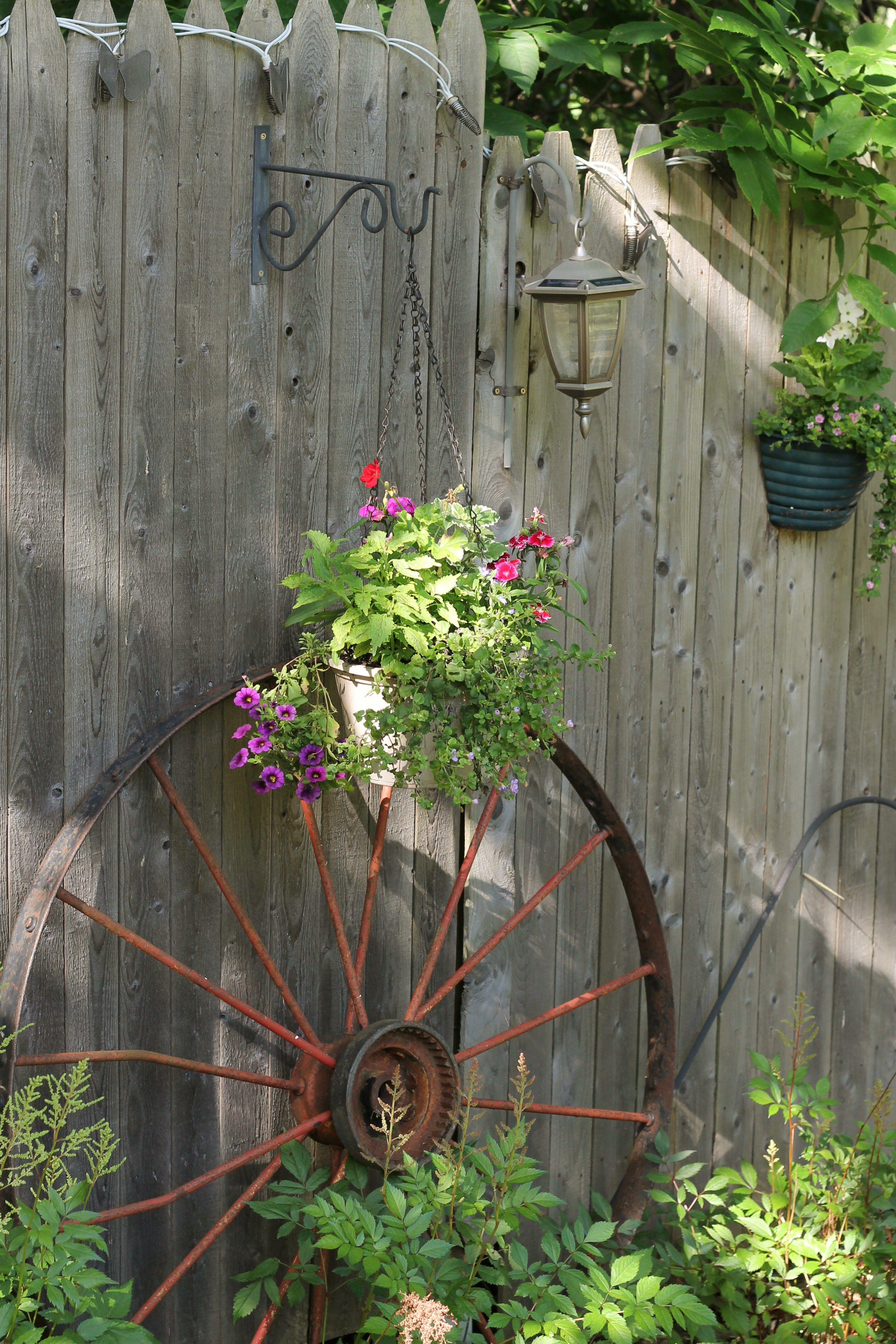 Old wagon wheel up against an old rustic fence. | Rustic ...