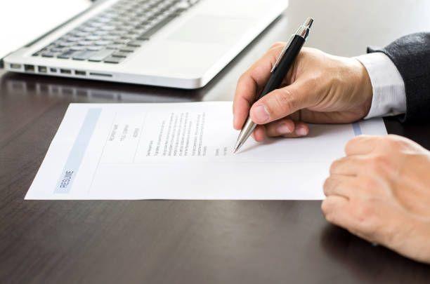 closeup businessman or job seeker signing on resume form