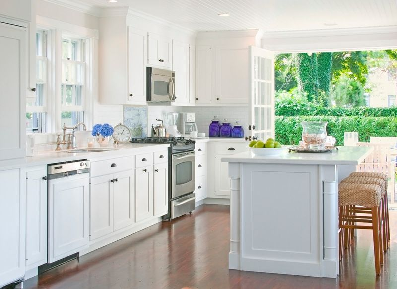 White kitchen with stainless steel appliances and wood floors ...