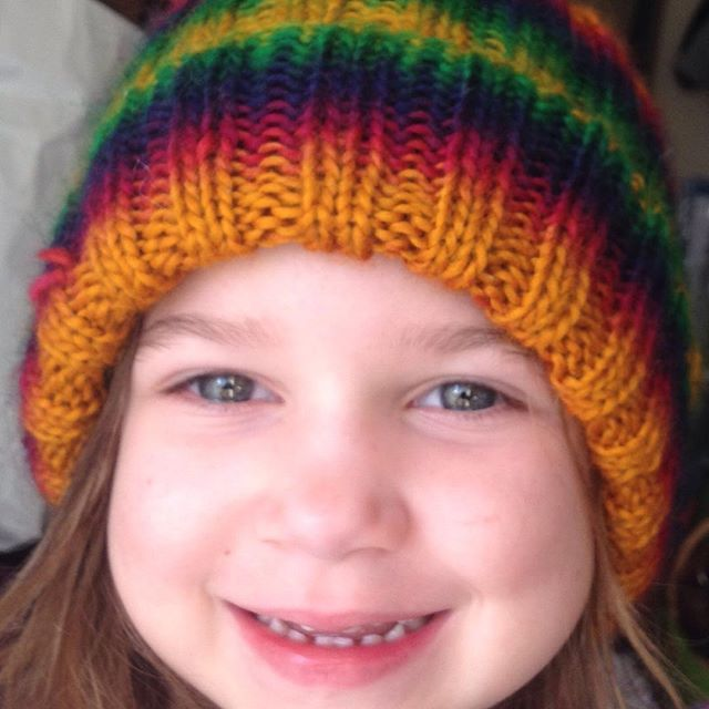 """Rainbow Hat"" for my daughter Alyx. She was very pleased with it. :) Yarn is Schoppel-Wolle Reggae Ombré colorway #1505 Kunterbunt (Motley) 100% Merino Wool. This project took just over one skein. #rainbowhat #selfstriping #ribstitch #schoppelwolle #reggaeombre #merino #alyx #knittingmama #happycustomer"
