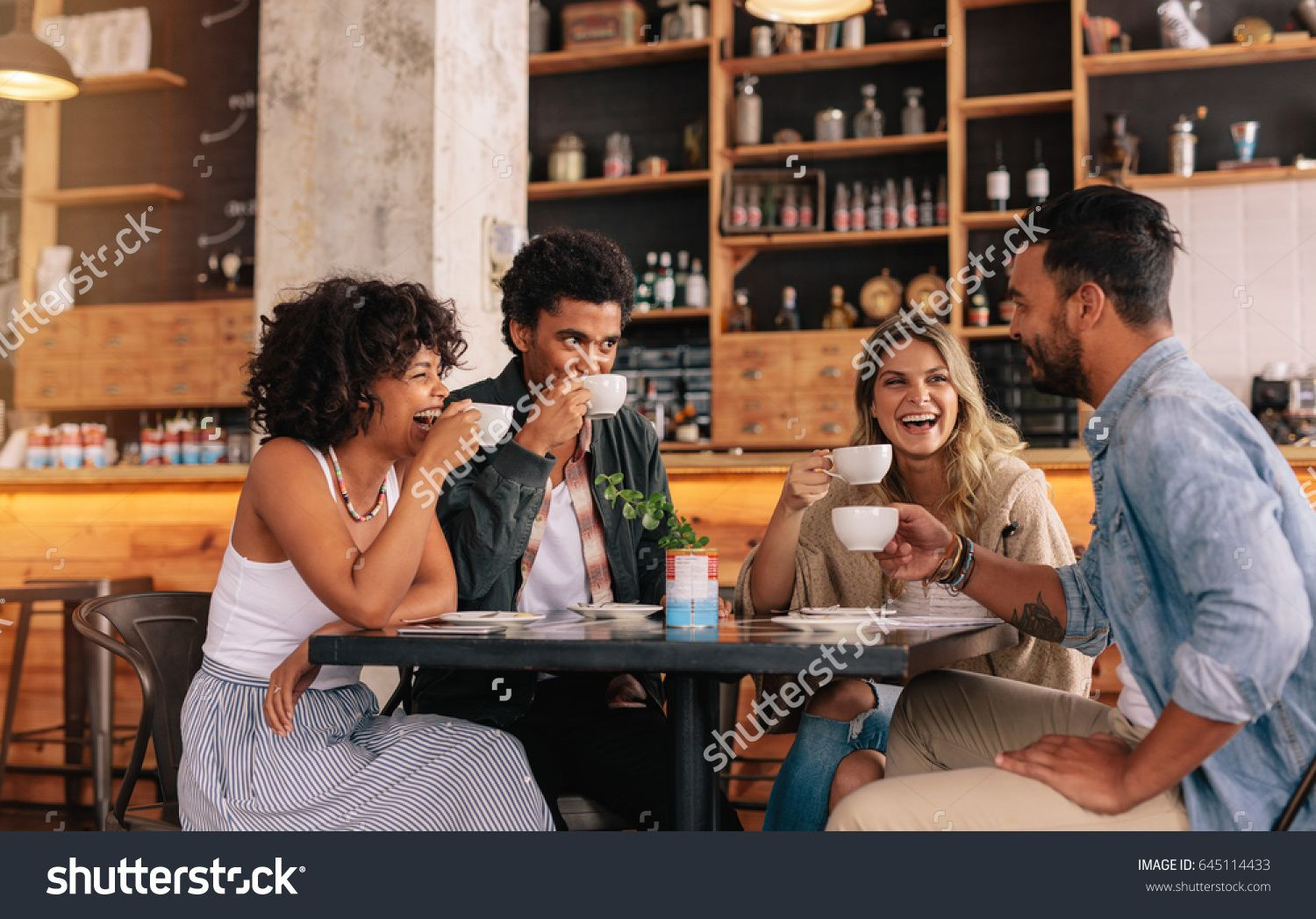 Diverse group of friends enjoying some coffee together in a restaurant and  talking. Young people sitting around cafe table and drinking coffee.