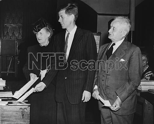John F. Kennedy, (center), 29, war veteran and son of Joseph P. Kennedy, former Ambassador to Great Britain, casts his vote on June 18, 1946 in Boston, MA, in primary election in which he is running as a democratic candidate for Congress in the 11th district, a post now held by Boston Mayor James M. Curley (D). Young Kennedy is accompanied by his grandparents, former Boston Mayor John F. Fitzgerald (right), and Mrs. Fitzgerald (left).