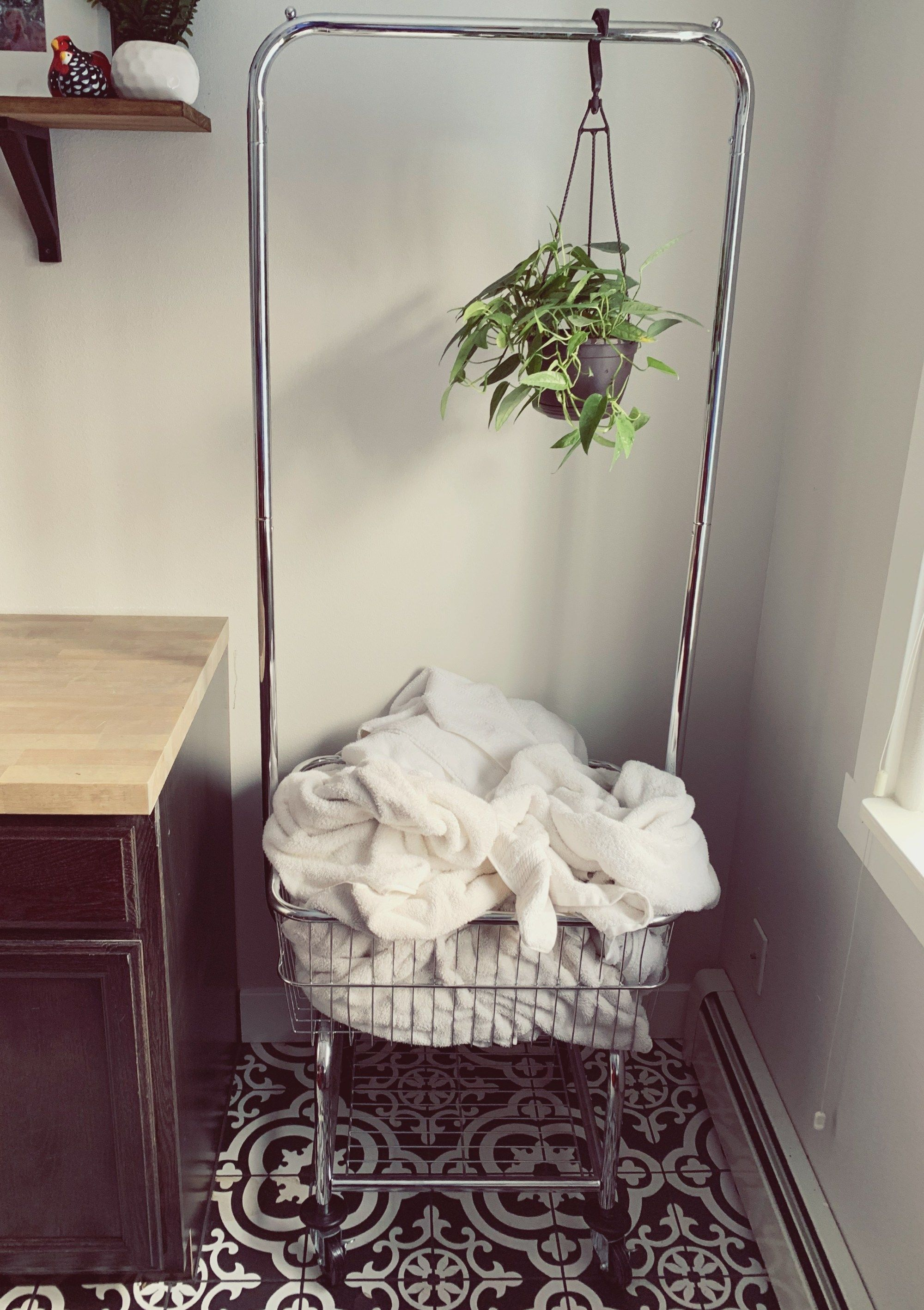 A Rolling Laundry Basket With Hanging Rack In Farmhouse Laundry