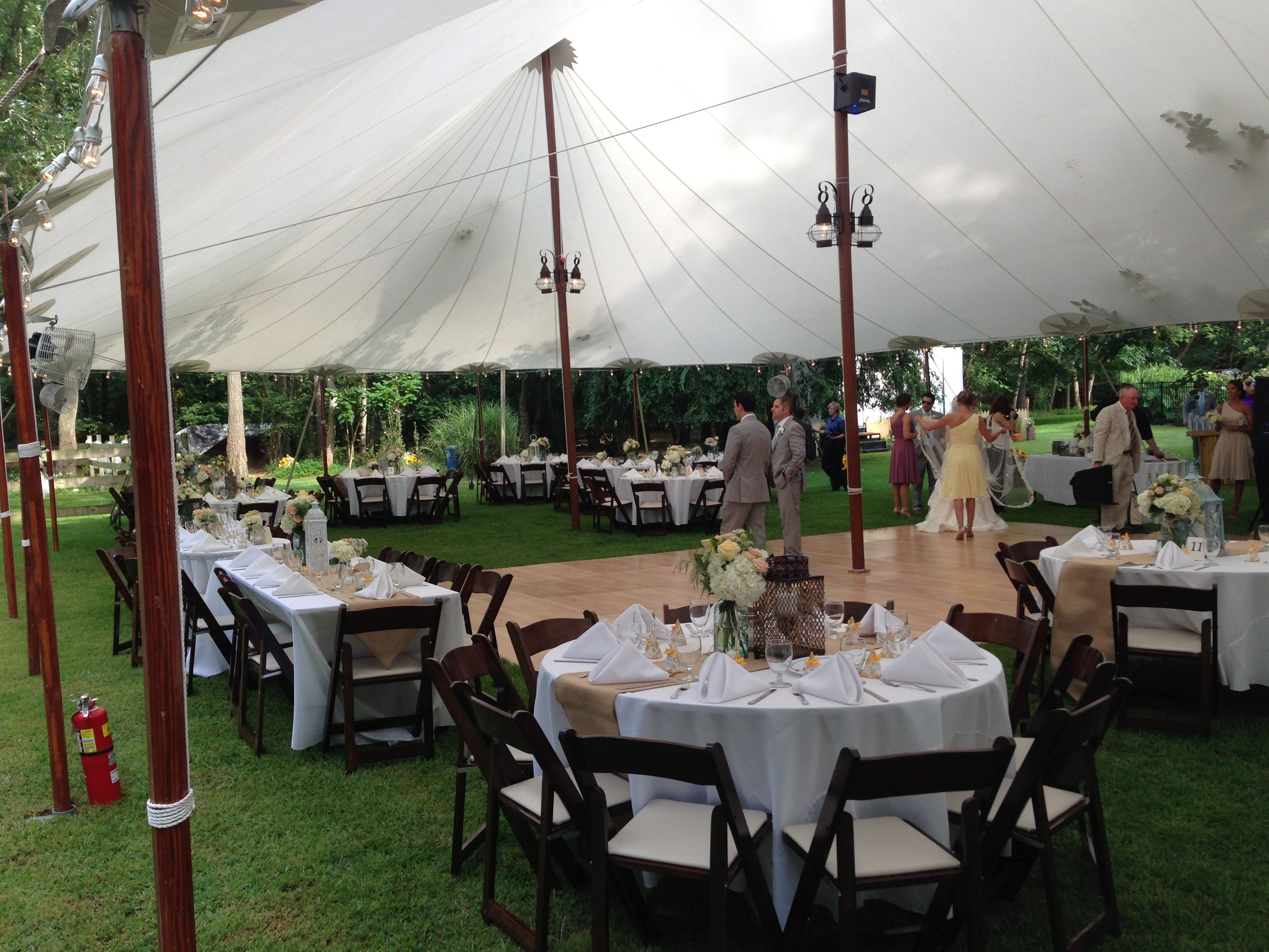 an elegant tented wedding. White table cloths with burlap runners and dark wood chairs make for elegant seating in a backyard setting www.TheLoftFlorist.com
