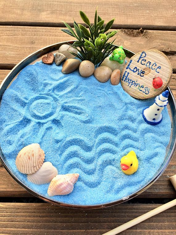 Mini Zen Garden, Ocean, Desk Accessory, DIY Zen Kit, Sand Therapy, Sand Art, Zen Gift, Coworker Gift, Zen Garden, Fairy Garden Kit is part of Zen garden Box - beach theme   Light Blue Sand Kit! We have 2 Ocean Zen Garden Kits so make sure it's the right color of sand   Create your own beach scene and designs in the sand with the wooden zen rake  Arrange the pebbles, shells and miniatures as much as you like to reflect your mood  It's therapeutic to create a design or message and get lost playing in the sand  Comes with a Mini Wood Slice to use as a prop or WRITE YOUR OWN MESSAGE WITH A SHARPIE!!!!!! Great for kids, adults and very popular as a coworker gift   Each garden kit comes with LIGHT BLUE SAND included 1 fake plant Baggie filled with Pebbles and Sea Shells 1 plastic bowl (5inch diameter) 1 Lighthouse 1 Duck 1 Ladybug as ladybugs bring good luck 1 Wooden Heart engraved with  Love  1 Wood slice to create a message 1 Zen Rake to create your sand designs Each zen garden comes as a complete kit and ready for you create it right away  The kit comes in a beautiful teal box with a coral bow   Gift Wrapping is available where we add a tag with To and From   Check out our other garden kits! We have a Fairy, Dinosaur and Winter garden kits all ranging from $10$30 www partynwithplants com