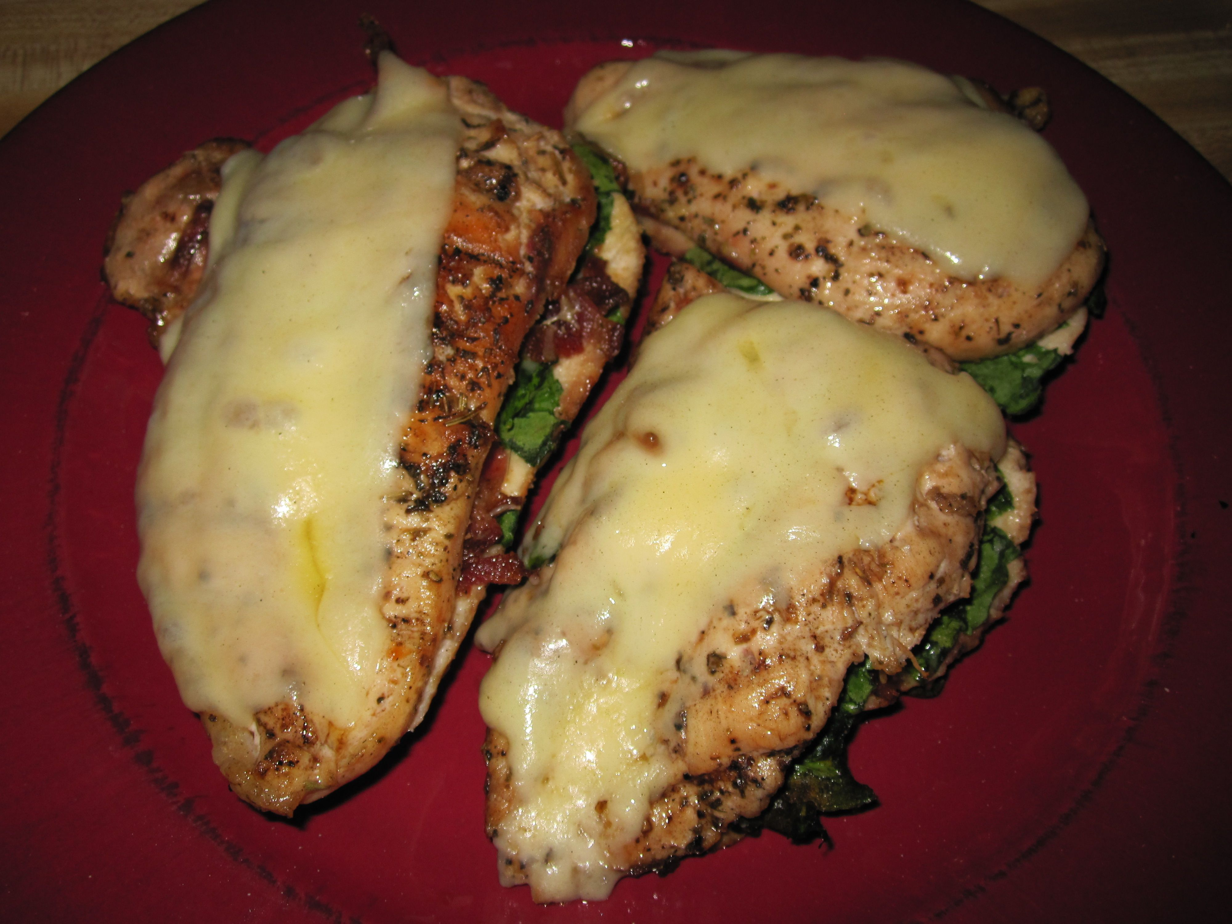 Grilled chicken breasts stuffed with bacon and spinach, topped with cheese.