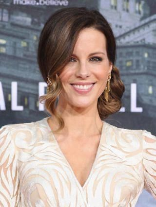 Kate Beckinsale's wavy side bun is oh-so-glamorous—and only requires a curling iron to get the look. DIY: Leave your bangs out and gather your hair into a low side pony. Holding a one-inch barrel curling iron vertically, add some curl your ponytail. Try Solano Spring 1 inch Professional Curl, $79, solanopower.com. Next, soften the curls with a brush and lightly tease your pony to give it more volume. Then create a loose braid and twist it around your hair  #sideUpdos #lowsidebuns