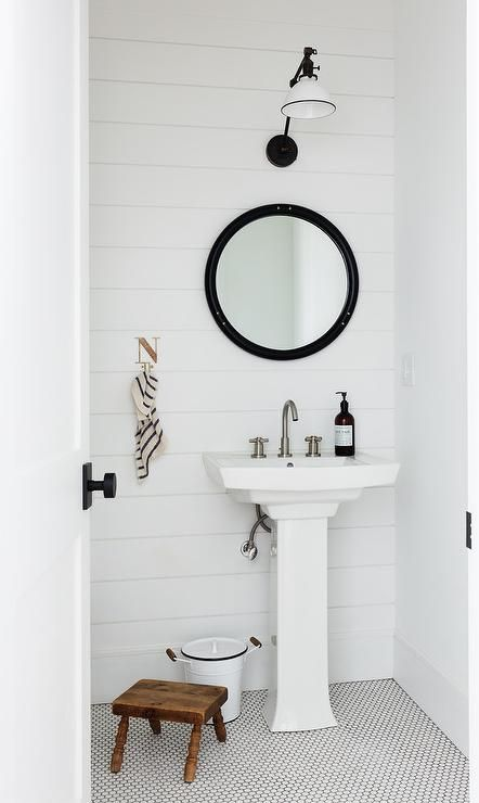 Cottage Powder Room Inspiration Featuring Shiplap Walls And A Round Black Mirror Above Pedestal Sink Illuminated By White Vintage Swing Arm