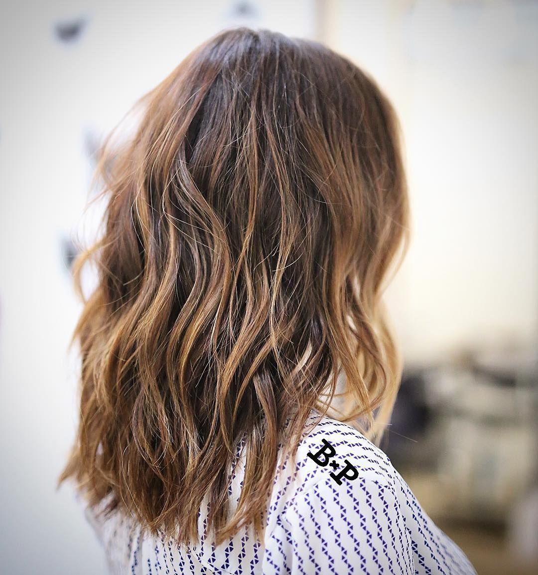 wavy chestnut-brown collarbone-length hair with caramel