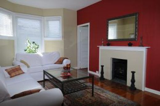 A cheerful living room featuring a bright red accent wall ...
