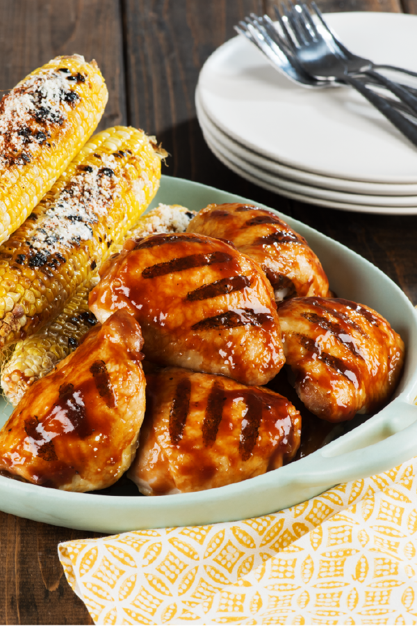 Wood-Smoked BBQ Chicken Thighs with Spicy Charred Corn – We're convinced that your dinner table wouldn't be complete without this savory recipe for saucy grilled chicken and parmesan cheese topped corn!