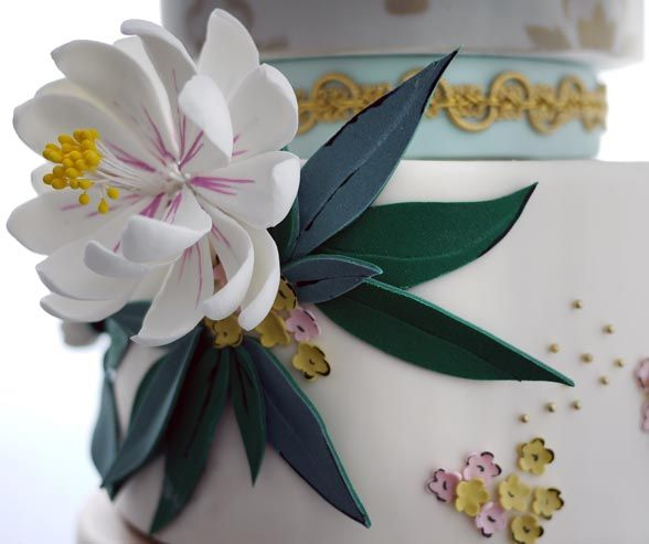A fondant water lily draws attention to the middle tier of this wedding cake.