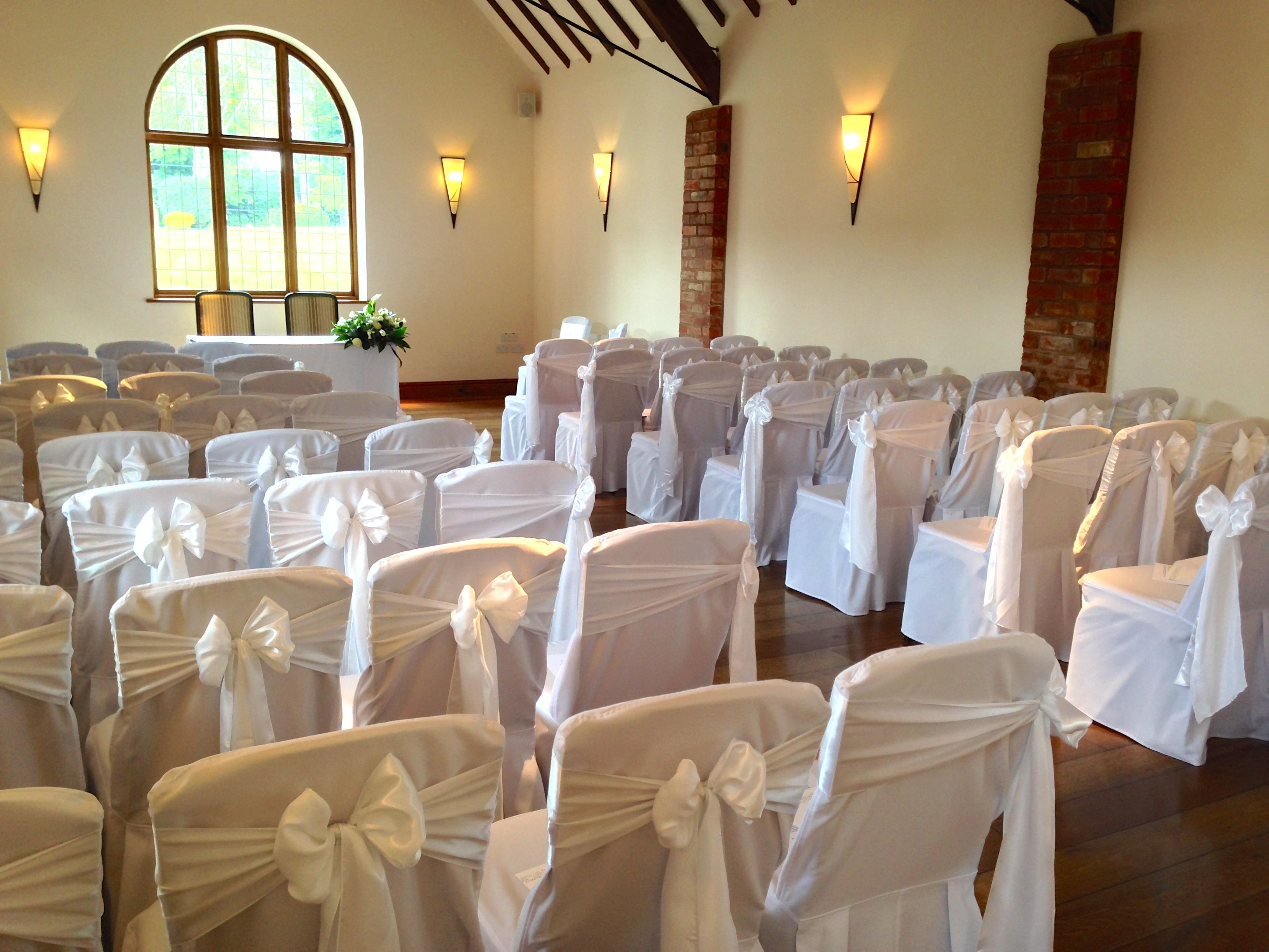 Chair covers with white satin sashes at Nuthurst Grange Provided